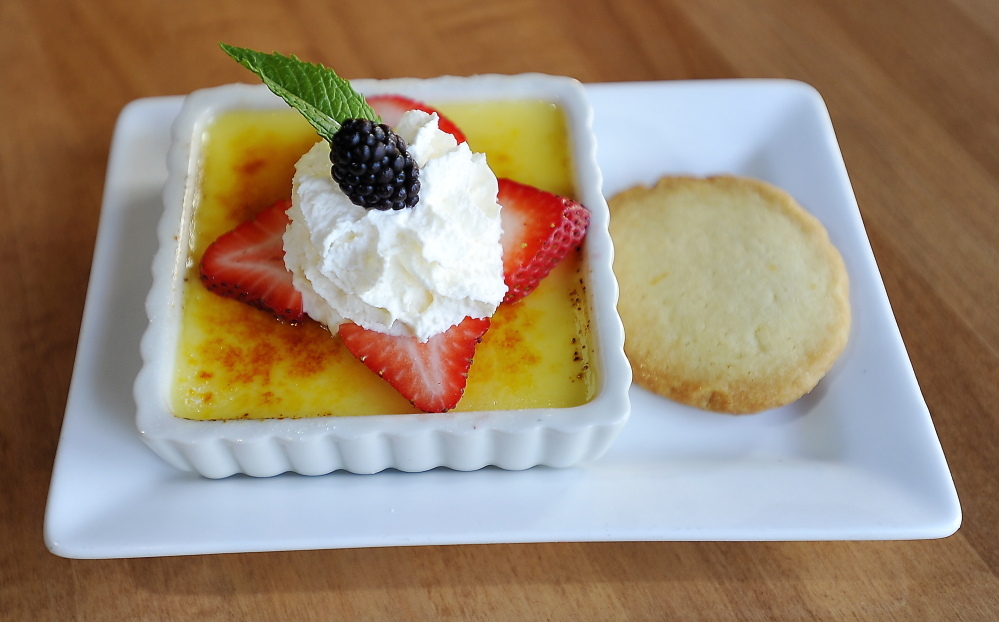 Vanilla creme brulee with Meyer lemon shortbread cookie and berry garnish.