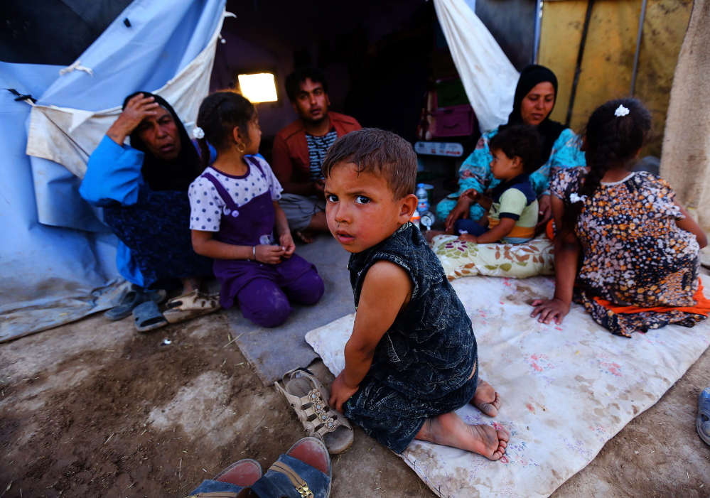 Iraqi refugees sit at the Khazir refugee camp outside Irbil in northern Iraq on Friday.