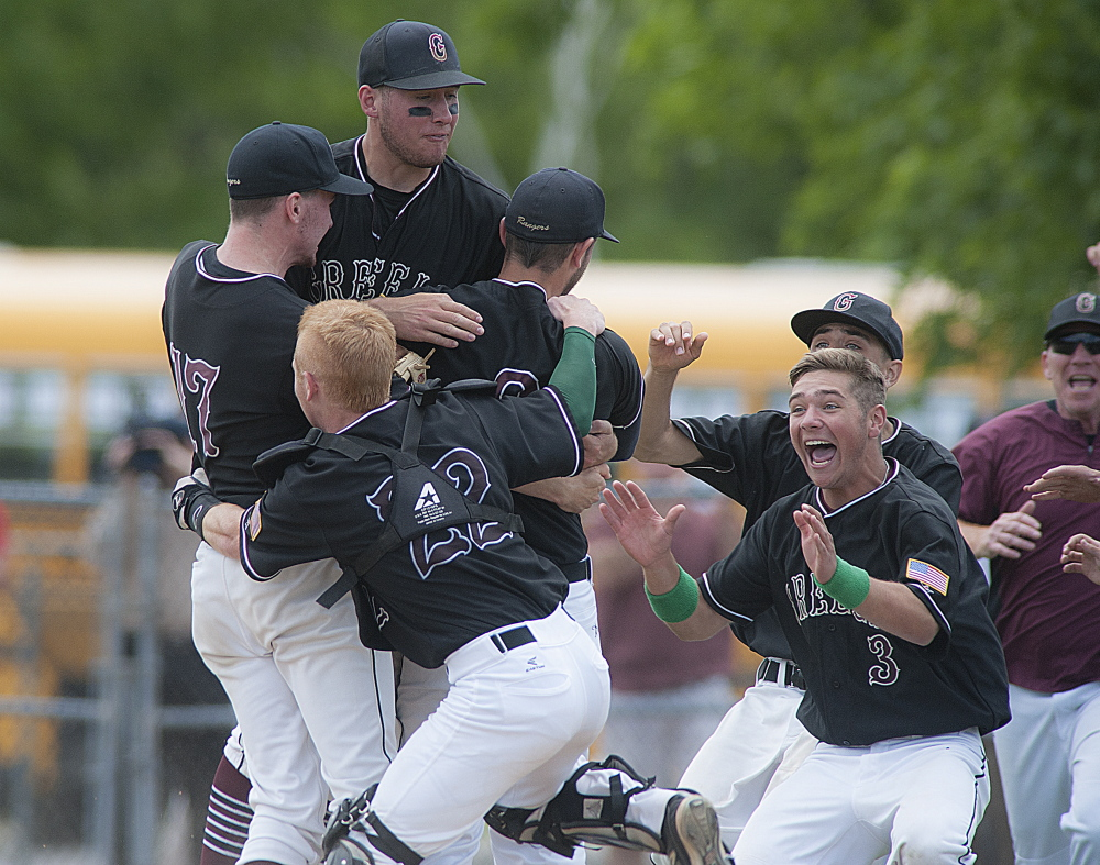 Greely pitcher Connor Russell, 9, is mobbed by teammates Mike McDevitt, back, third baseman Sam Porter, 17, catcher Reid Howland, 22, and Austin Nowinski, 3, after winning the state Class B baseball championship against Caribou 1-0 at Mansfield Stadium in Bangor on Saturday.