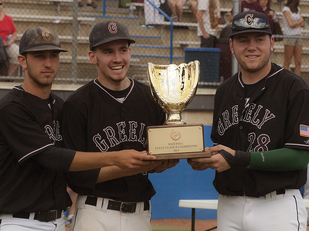 Greely's Connor Russell , left, Sam Porter, middle, and Bailey Train with the Class B baseball state trophy after defeating Caribou 1-0 at Mansfield Stadium in Bangor on Saturday.