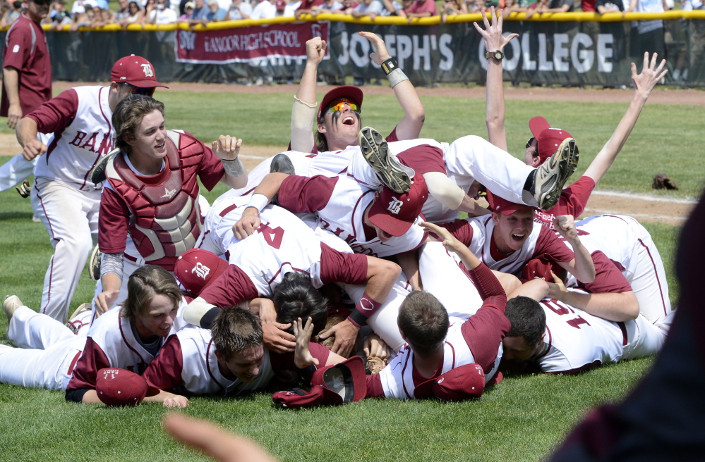 The Bangor baseball team, including catcher Hunter Boyce, left, and Sam Huston, center top, celebrate their 8 to 0 win over Windham for the Class A baseball state championship.