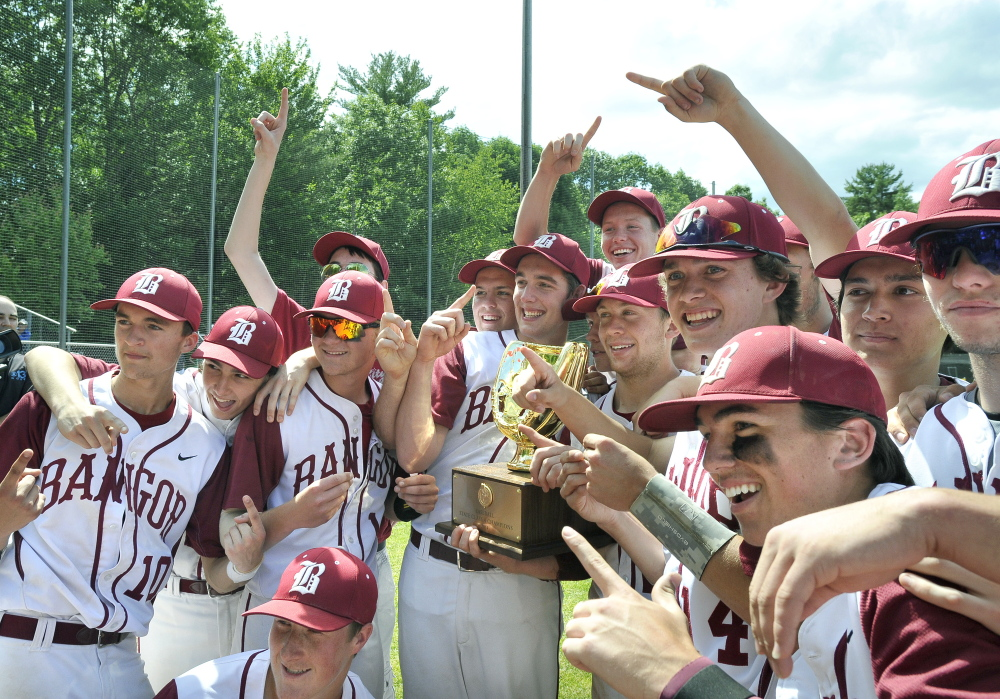 Members of the Bangor baseball team hoist the trophy for fans after defeating Windham for the Class A baseball state Championship Saturday at St. Joseph's College in Standish.