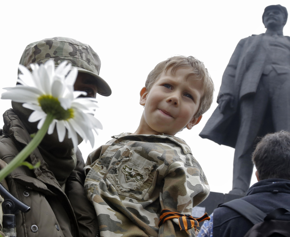 A pro-Russia fighter holds a boy on his hands after taking an oath in eastern Ukraine on Saturday with a statue of Soviet Union founder Vladimir Lenin on the right.