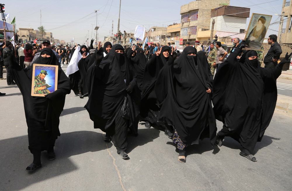"Supporters for the newly formed ""Peace Brigades"" participate in a parade in the Shiite stronghold of Sadr City, Baghdad, Iraq, Saturday."