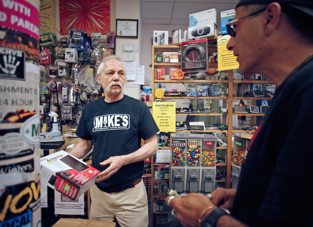 Mike Fink, owner of the Guitar Grave pawnshop in downtown Portland, sells a television antenna to Craig Campbell. Amelia Kunhardt/Staff Photographer