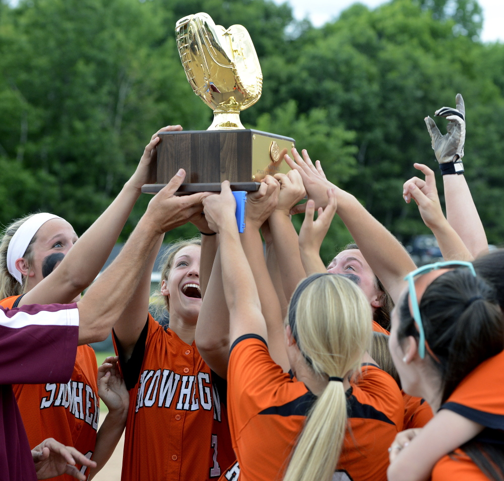 Skowhegan players raise the championship trophy after beating Thornton Academy for the Class A softball state championship at St. Joseph's College.