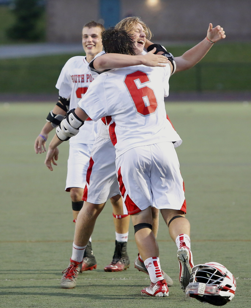 Duncan Preston, who paced the South Portland offense with four goals, hugs goalie T-Moe Hellier after the Red Riots capped a 14-1 season with their first lacrosse state championship.