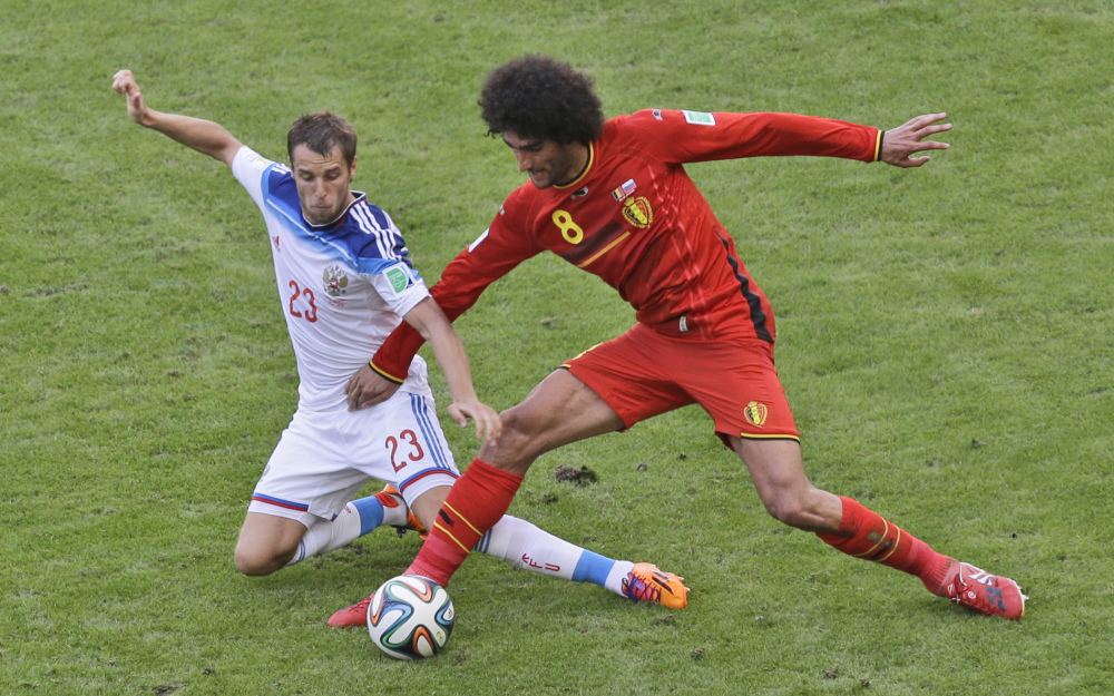 Russia's Dmitry Kombarov, left, and Belgium's Marouane Fellaini challenge for the ball during Sunday's World Cup game at Rio de Janeiro, Brazil. Belgium won, 1-0.