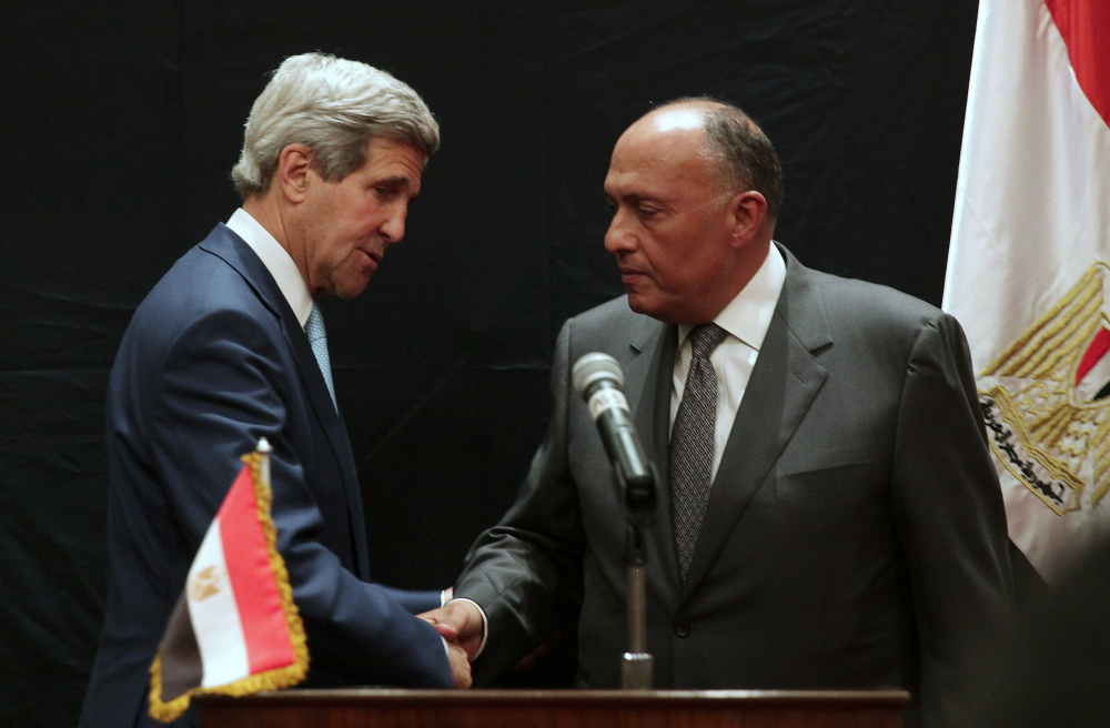 """U.S. Secretary of State John Kerry, left, shakes hands with Egyptian Foreign Minister Sameh Shoukry following a joint news conference on Sunday in Cairo, Egypt. Shoukry welcomed Kerry's visit as important for ties between the two governments. """"I hope we will have a fruitful discussion here,"""" he said."""