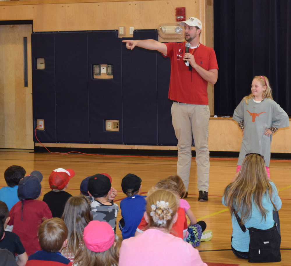 Three-time Olympic gold medalist Ian Crocker addresses Wells Elementary School students in a special assembly recently. Crocker was invited to the school by third-grader Isabella Bazata (right), who detailed the Olympic swimmer's life as part of a social studies project on famous Mainers.