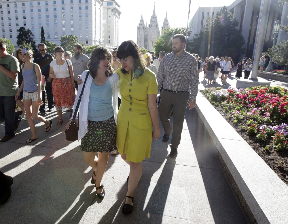 Kate Kelly, right, walks with a supporter after addressing her supporters at the Church Office Building of the Church of Jesus Christ of Latter-day Saints during a vigil Sunday, June 22, 2014, in Salt Lake City. Kelly was shocked to find out earlier this month from her bishop that she is facing excommunication from The Church of Jesus Christ of Latter-day Saints, of which she is a lifelong member.