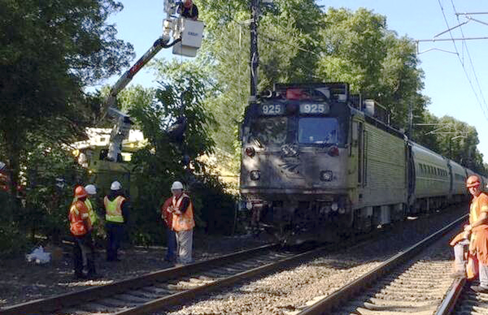 Officials work at the scene Monday where an Amtrak train struck a vehicle overnight in Mansfield, Mass. Three people in the vehicle were killed. Service on Amtrak and MBTA lines was delayed.