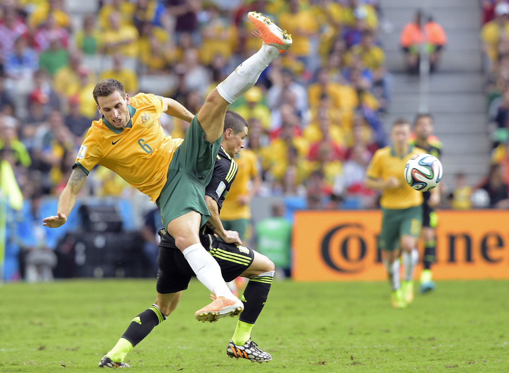 Australia's Matthew Spiranovic and Spain's Fernando Torres fight for the ball during the group B World Cup soccer match between Australia and Spain at the Arena da Baixada in Curitiba, Brazil, Monday.