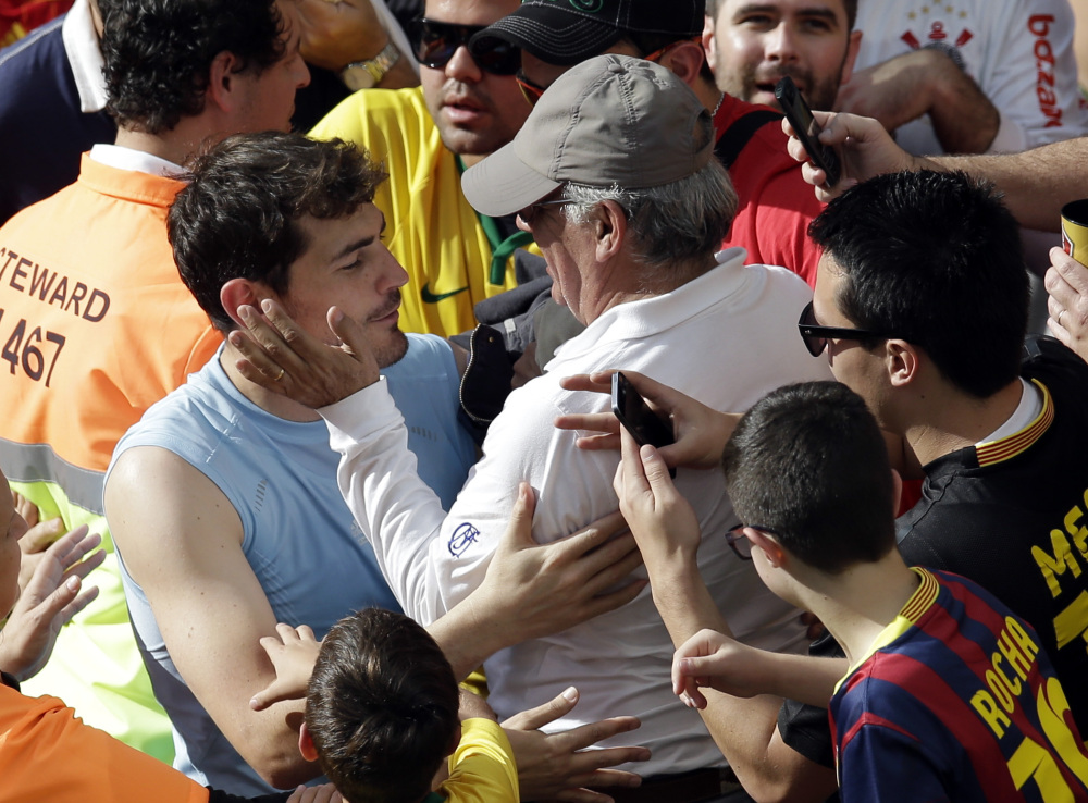 Spain's goalkeeper Iker Casillas is greeted by a member of the crowd after the group B World Cup soccer match between Australia and Spain at the Arena da Baixada in Curitiba, Brazil, Monday, June 23, 2014.