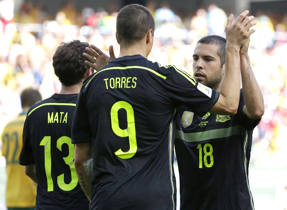Spain's Fernando Torres, center, celebrates with teammate Jordi Alba after scoring during the group B World Cup soccer match between Australia and Spain at the Arena da Baixada in Curitiba, Brazil, Monday, June 23, 2014.