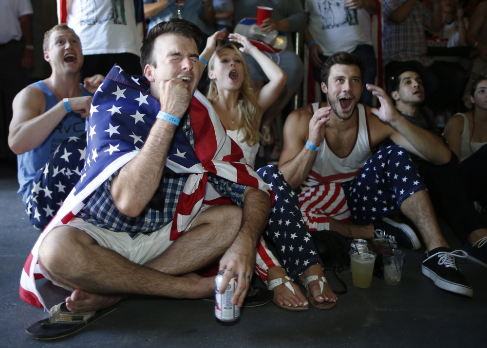 USA soccer fans (L-R) Reid Boutte, 25, McKenzie Anderson, 23, and Andy Shephard, 25, react during the 2014 World Cup Group G soccer match between Portugal and the U.S. at a viewing party in Los Angeles, California, Sunday.