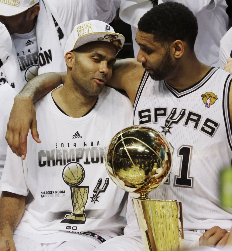 San Antonio Spurs guard Tony Parker, left, and forward Tim Duncan celebrate after Game 5 of the NBA basketball finals on Sunday, June 15, 2014, in San Antonio. The Spurs won their fifth championship in 15 years.