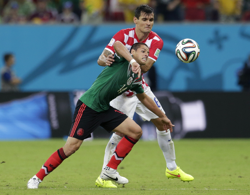 Mexico's Javier Hernandez, front, is held back by Croatia's Dejan Lovren during the group A World Cup soccer match.