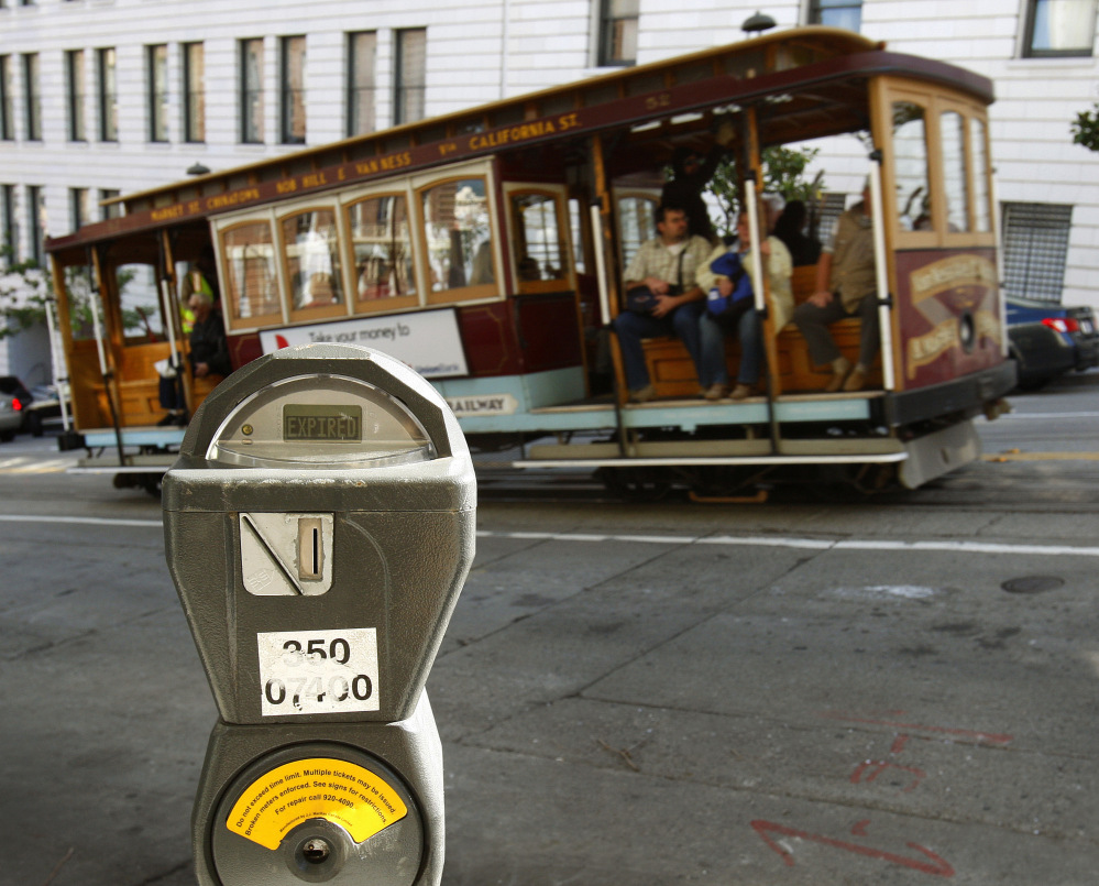 A cable car passes a parking meter near San Francisco's financial district. San Francisco City Attorney Dennis Herrera on Monday issued a cease-and-desist demand to a mobile app called Monkey Parking, which allows people to auction off public parking spaces that they're using to other nearby drivers.