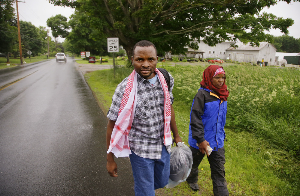 Somali refugee Adan Abdi, left, walks with his wife, Fatumo Mohamed, back to her car after a rainy afternoon forced an early end to her work day as a farm hand on Red Fire Farm in Montague, Mass. Abdi works the graveyard shift in the maintenance department of a local hospital. The couple has three children.