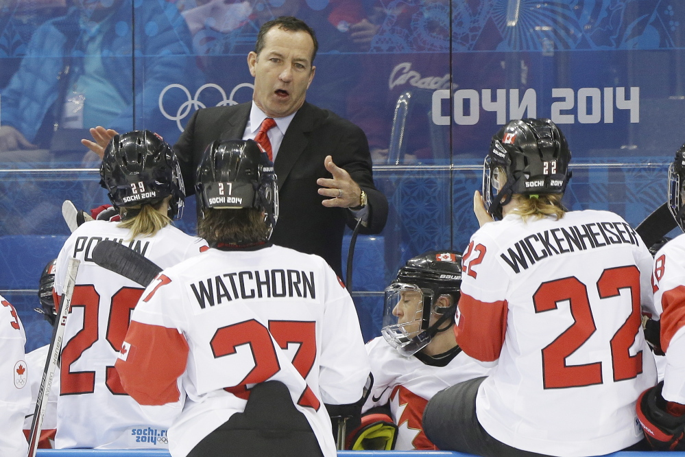 Canada head coach Kevin Dineen talks to the team during a break in the action against Switzerland in the 2014 Winter Olympics women's semifinal hockey game in Sochi, Russia. The Associated Press