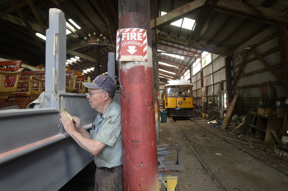 "Don Curry, the restoration project manager at the Seashore Trolley Museum, sands the side of the 1906 Montreal ""Golden Chariot"" observation car at the Seashore Trolley Museum in Kennebunkport on Thursday."