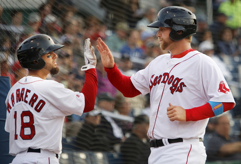 Dave Chester of the Portland Sea Dogs, right, is welcomed Monday night by Deven Marrero after scoring on a single by Heiker Meneses in the second inning of a 3-2 victory against the New Hampshire Fisher Cats at Hadlock Field. The Sea Dogs reached 50 wins and continue to hold a six-game lead over Binghamton in the division.