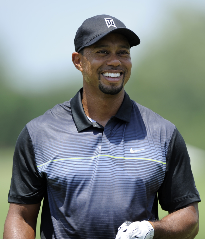 Tiger Woods smiles on the driving range during a practice round for the Quicken Loans National golf tournament, Tuesday, June 24, 2014, in Bethesda, Md.