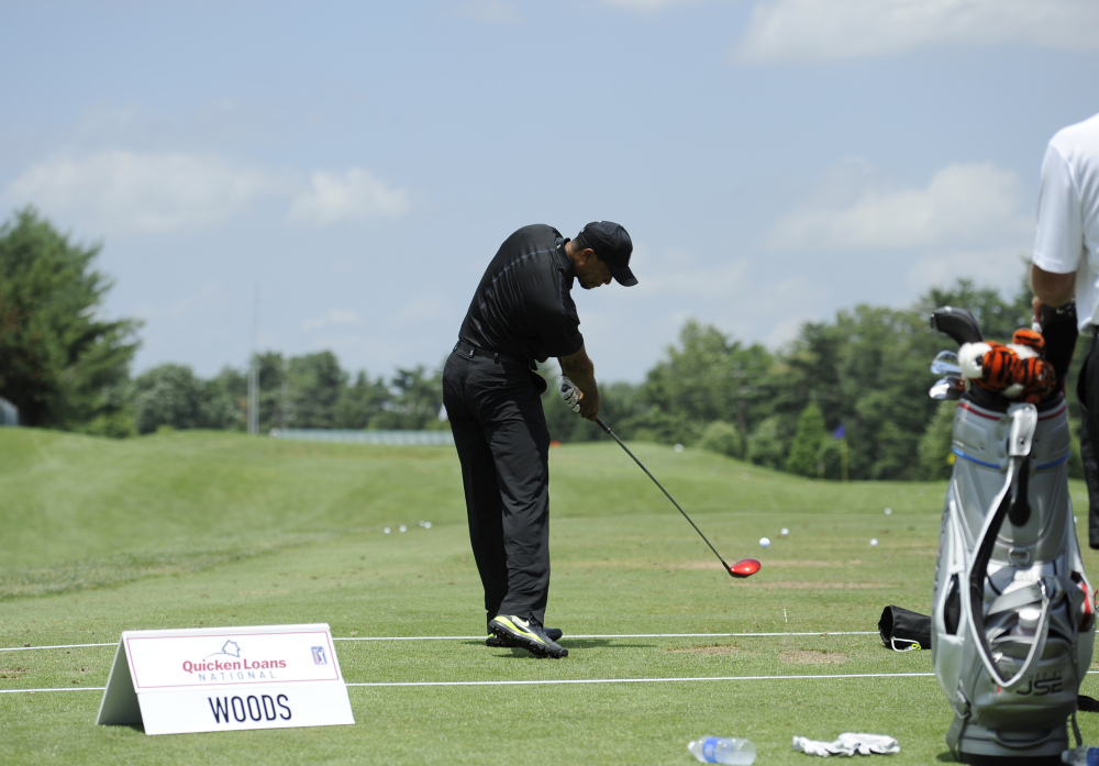 Tiger Woods takes a swing at the driving range during practice round for the Quicken Loans National golf tournament.