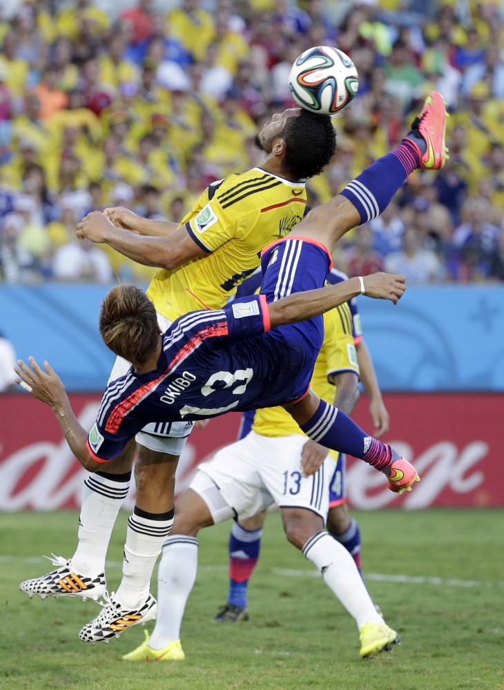 Japan's Yoshito Okubo shoots next to Colombia's Carlos Valdes during the group C World Cup soccer match between Japan and Colombia.