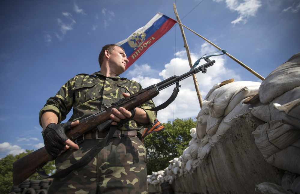 A pro-Russian separatist guards a road checkpoint in the Luhansk region of eastern Ukraine, on Sunday. A cease-fire in Ukraine is thrown into peril by a helicopter attack.