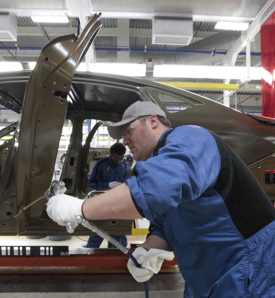 In this March 14, 2014 photo, an assembly line worker works on a 2015 Chrysler 200 automobile at the Sterling Heights Assembly Plant in Sterling Heights, Mich. Most economists agree that the economy last quarter was depressed by temporary factors _ particularly the blast of Arctic chill and snow that shuttered factories, disrupted shipping and kept Americans away from shopping malls and car dealer lots. Since then, the picture has brightened. (AP Photo/Paul Sancya)