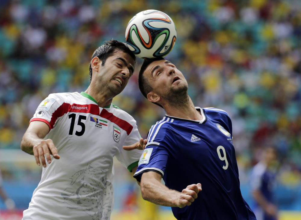 Iran's Pejman Montazeri, left, and Bosnia's Vedad Ibisevic battle for the ball during a group F World Cup soccer match between Bosnia and Iran at the Arena Fonte Nova in Salvador, Brazil, Wednesday, June 25, 2014.