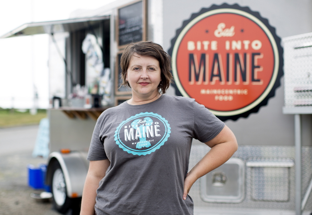 "Sarah Sutton takes a break from selling lobster rolls from her Bite Into Maine food truck at Fort Williams Park on Wednesday. ""We have the best office view ever!"" she said."