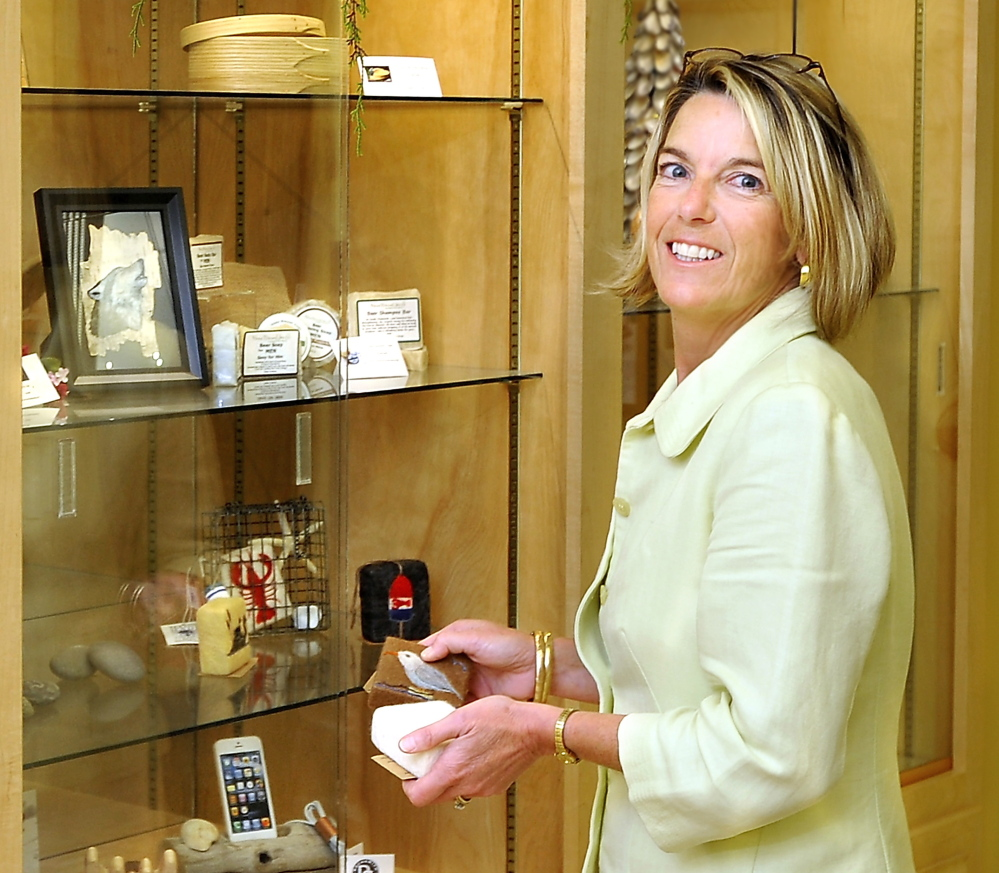 Tammy Knight rotates products in and out of a display case at the State Office Building.