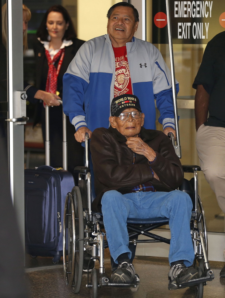 Phillip Coon, a World War II veteran and prisoner of war who survived the Bataan Death March, is pushed in his wheelchair by his son Michael Coon as he returns home from Japan at the Tulsa International Airport in Tulsa, Okla., in 2013. The Muscogee Creek Nation says tribal member Phillip Coon died Monday in Tulsa. Coon was the last remaining Native American survivor of the Bataan Death March, where thousands of soldiers were forced on a 65-mile trek by the Japanese military.