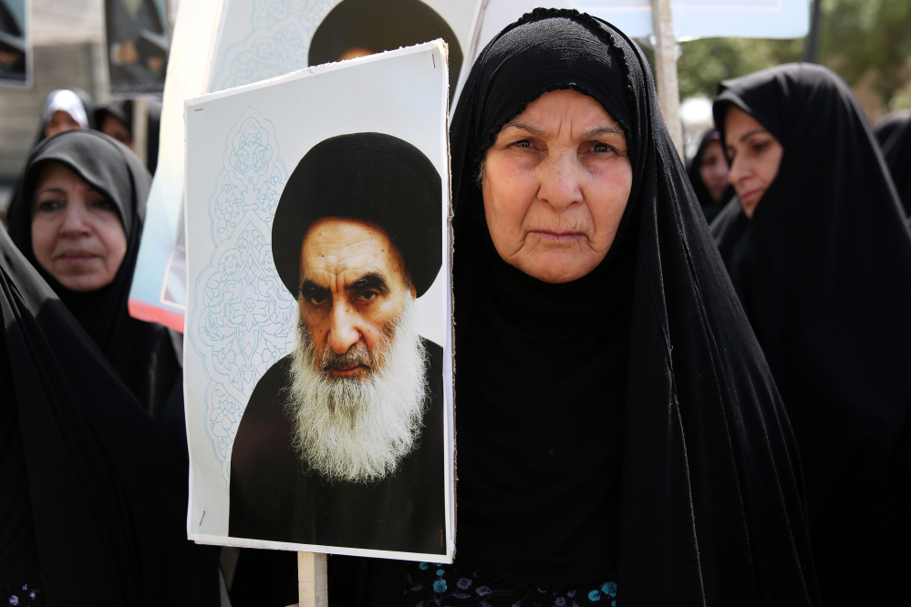 An Iraqi woman living in Iran holds a poster of the Grand Ayatollah Ali al-Sistani, Iraq's top Shiite cleric, in a demonstration against Sunni militants of the al-Qaida-inspired Islamic State of Iraq and the Levant, or ISIL, and to support Ayatollah al-Sistani, in Tehran, Iran. Prominent Shiite leaders pushed Thursday for the removal of Iraqi Prime Minister Nouri al-Maliki.