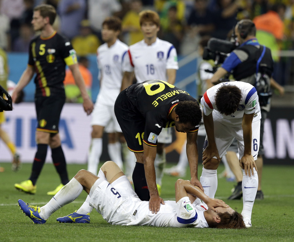 Belgium's Mousa Dembele helps console South Korea's Kim Young-gwon following Belgium's 1-0 victory over South Korea during the group H World Cup soccer match at the Itaquerao Stadium in Sao Paulo, Brazil, on Thursday.