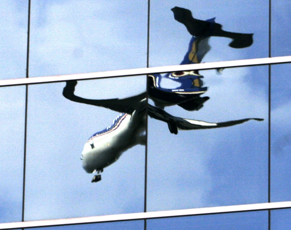 A  passenger jet landing at Washington's Reagan National Airport in Roslyn, Va., is reflected in the mirrored windows of an office building.