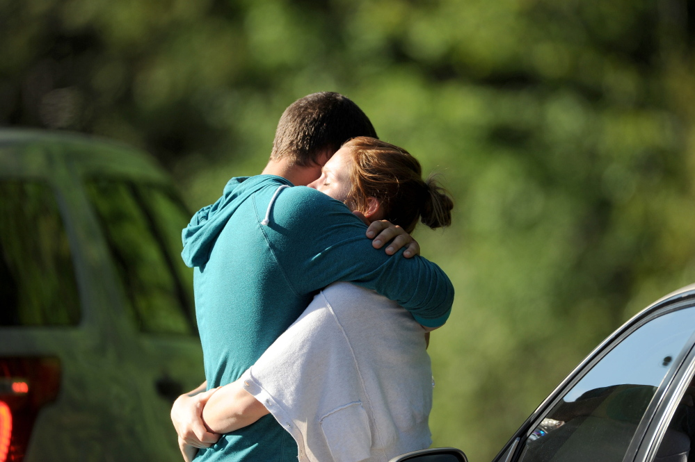 Staff photo by Michael G. Seamans A couple from Canada hug after witnessing a logging truck flip and hit an SUV on U.S. Route 201 in Moscow on Thursday.