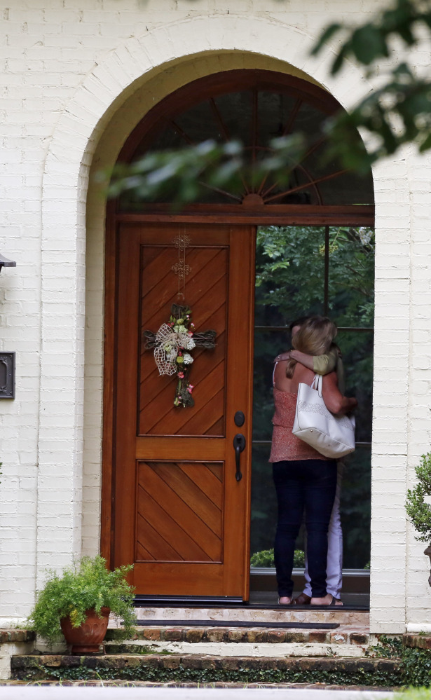 A visitor is hugged at the front door of the home of tea party official Mark Mayfield on Friday in Ridgeland, Miss., where he was found dead.