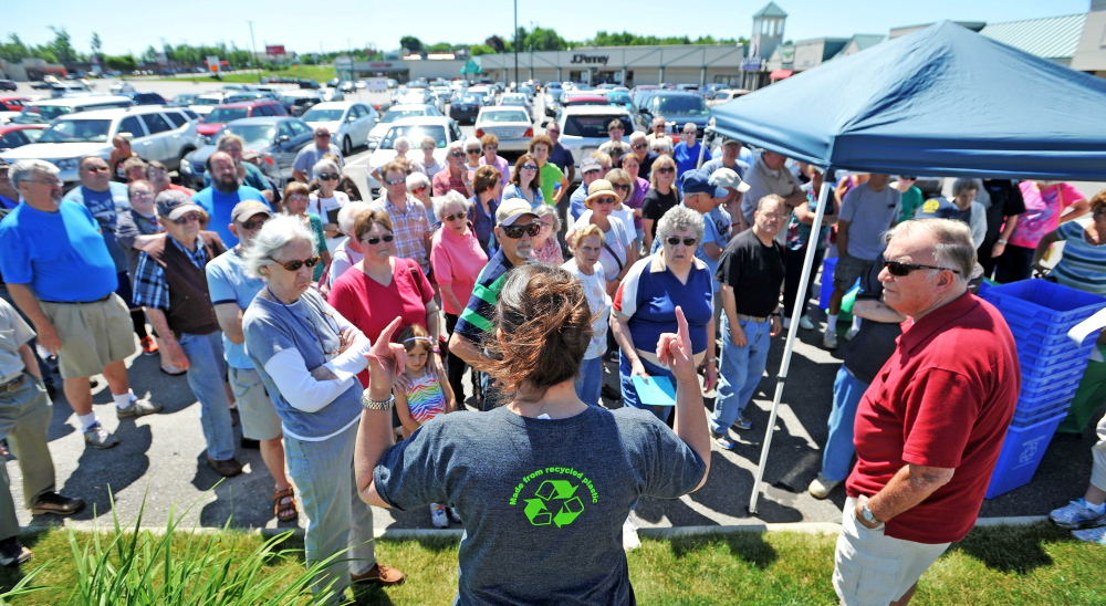 Lissa Bittermann, foreground, of Ecomaine, talks to Waterville residents Friday about the city's recycling program.