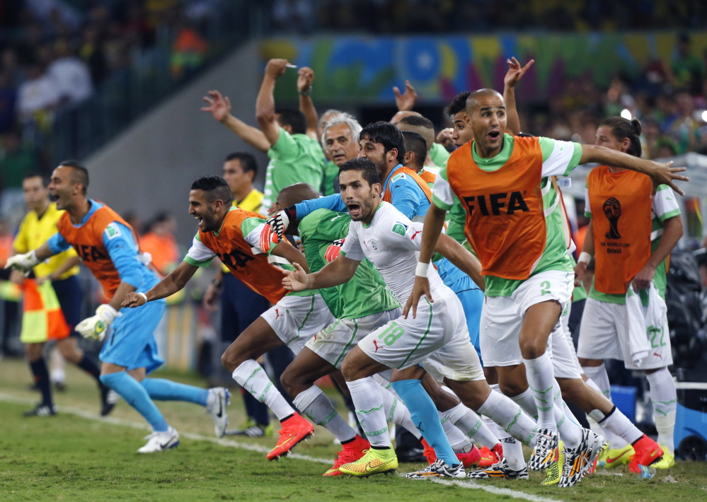 Algeria's bench players run onto the field Thursday in Curitiba, Brazil, to celebrate after their 1-1 draw with Russia allowed Algeria to qualify for the knockout stage. Coupled with Nigeria's earlier qualification, the World Cup has two African teams in the Round of 16 for the first time.