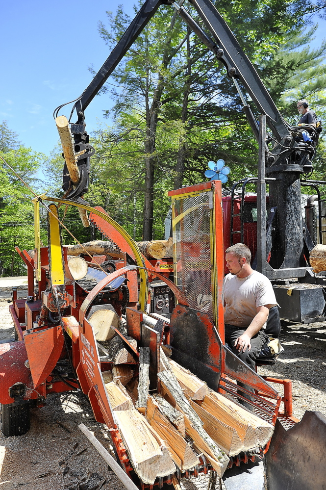 WINDHAM, ME - MAY 21: Mark Killinger, owner of Atlantic Firewood adds hardwood logs to the line as his son, Mike Killinger, owner of Maine Logging, tends the cutting and processing machine as they work together to cut and process firewood for sale. (Photo by Gordon Chibroski/Staff Photographer)