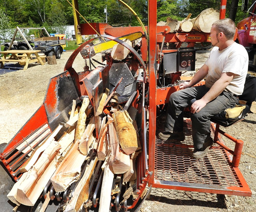 WINDHAM, ME - MAY 21:  Mike Killinger, owner of Maine Logging, works on the cutting machine as he works with his father to cut and process firewood for sale. (Photo by Gordon Chibroski/Staff Photographer)