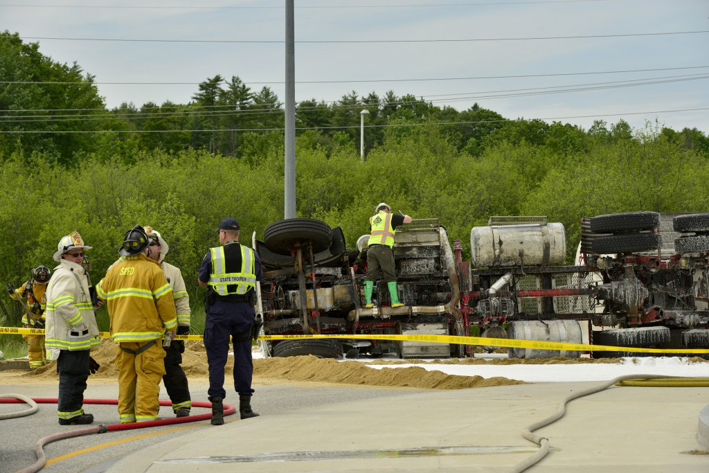 Emergency responders tend to a tractor-trailer truck carrying fuel that overturned on northbound Route 114 in Gorham on Wednesday.