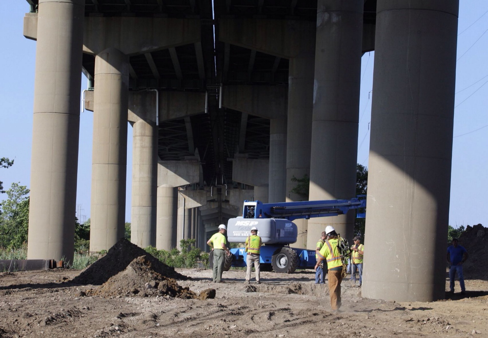 The Associated Press DelDot crew members surround a tilted column supporting a span of the I-495 bridge over the Christina River on Monday. The 4,800-foot bridge normally carries about 90,000 vehicles a day on I-495, which diverts traffic around the city of Wilmington.