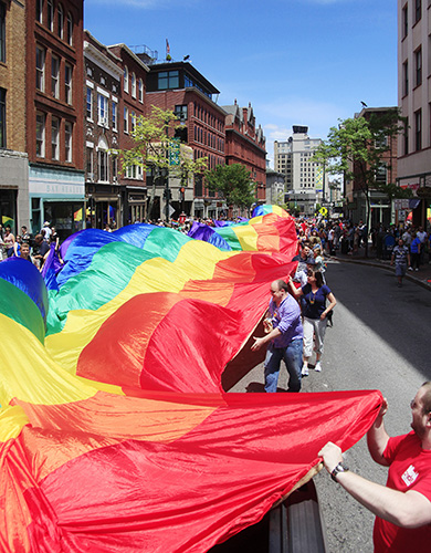 A 900-ft. Pride flag is carried by parade-goers as the Portland Pride Parade fills Congress Street in Portland Saturday. Jill Brady/Staff Photographer