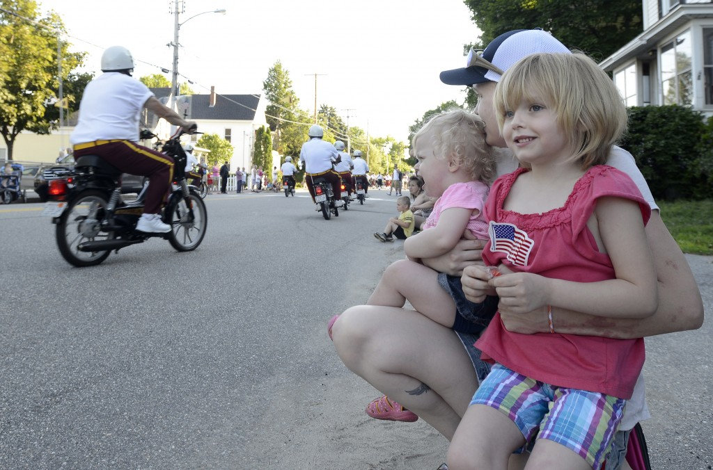 Kelly Hansen from Biddeford and her two daughters Ambyr, 16 months, and Aly, 6 years, watch the Shriner Mopeds race by during the La Kermesse parade along Alfred Street in Biddeford.