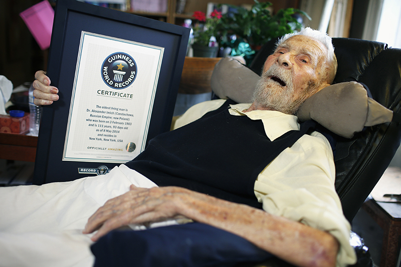 111-year-old Alexander Imich holds a Guinness World Records certificate recognizing him as the world's oldest living man during an interview with Reuters at his home on New York City's upper west side, May 9, 2014. REUTERS